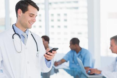 telefonos movil: M�dico de mensajes de texto con el grupo alrededor de la mesa en el fondo en el hospital