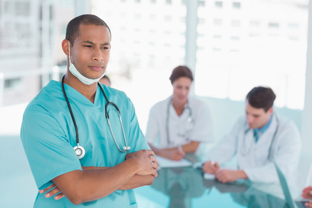 Serious male surgeon standing with group around table in background at hospital photo
