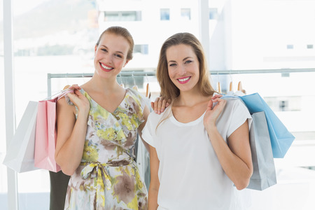 Portrait of two happy young women with shopping bags in the clothes store photo
