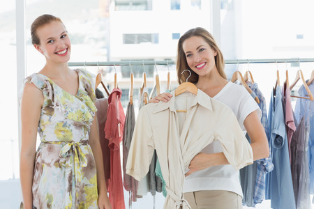 Two happy young women shopping in clothes store photo