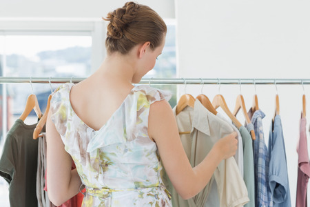 Rear view of a young female customer selecting clothes at clothing rack in store photo
