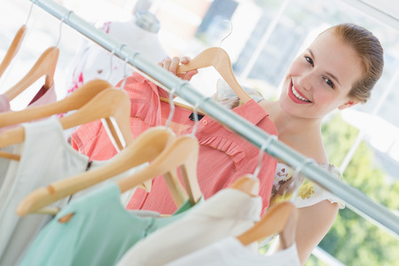 Close-up portrait of happy female customer selecting clothes at clothing rack in store photo