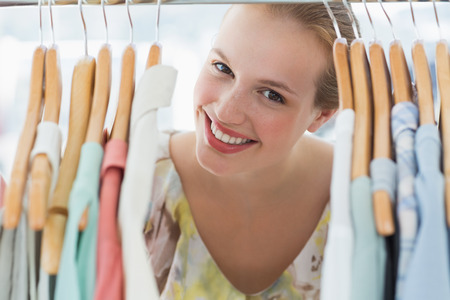Close-up portrait of happy female customer amid clothes rack photo