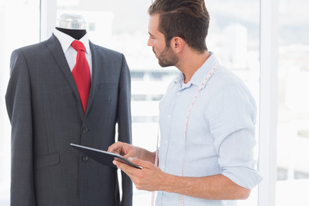 Concentrated young male fashion designer with digital tablet looking at suit on dummy in the studio Stock Photo - 27051717