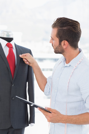 Concentrated young male fashion designer with digital tablet looking at suit on dummy in the studio Stock Photo - 27051718