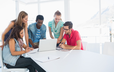 focus group: Group of young casual people using laptop in a bright office