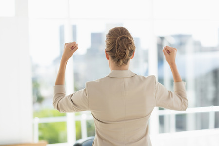 clenching fists: Rear of a cheerful young businesswoman clenching fists in a bright office