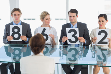well dressed  holding: Group of panel judges in a row holding score signs Stock Photo