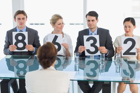 comit� d entreprise: Groupe de juges de panneaux dans une rang�e tenant des signes de pointage