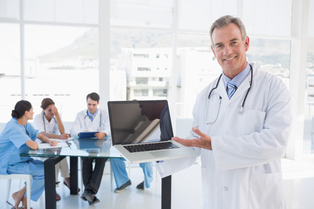 Doctor holding laptop with group around table in background at hospital photo