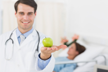 Portrait of a smiling doctor holding apple with patient in background at hospital photo