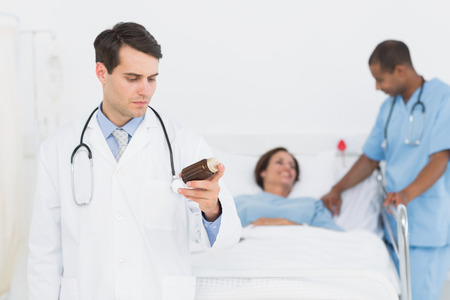 Serious doctor holding a bottle of pills with patient in background at hospital photo