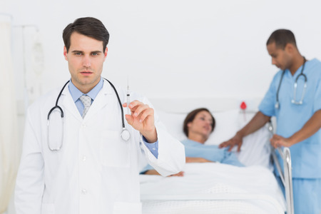 Serious doctor holding a syringe with patient in background at hospital photo