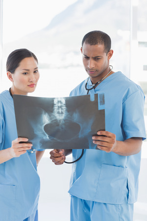 Two surgeons examining x-ray in a bright hospital photo