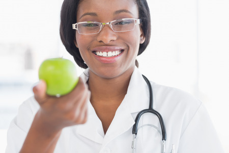 Portrait of a smiling female doctor holding an apple at a bright hospital photo