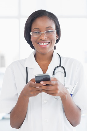 Smiling female doctor holding a mobile phone in the hospital photo