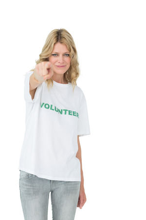 Portrait of a happy female volunteer pointing at you over white background photo