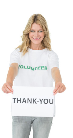 Smiling young female volunteer holding thank you paper over white background photo