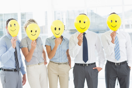 Group of business people holding happy smiles in front of their faces in a bright office photo