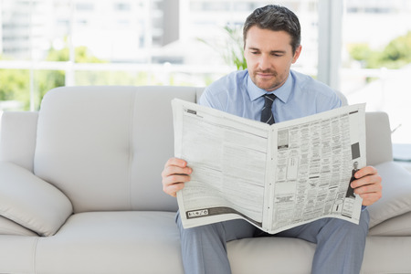 well read: Well dressed relaxed young man reading newspaper on sofa in the house