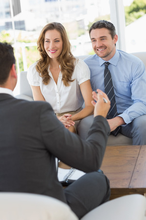 Smiling young couple in meeting with a financial adviser at home photo