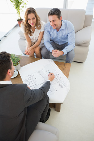 High angle view of a smiling young couple in meeting with a financial adviser at home photo