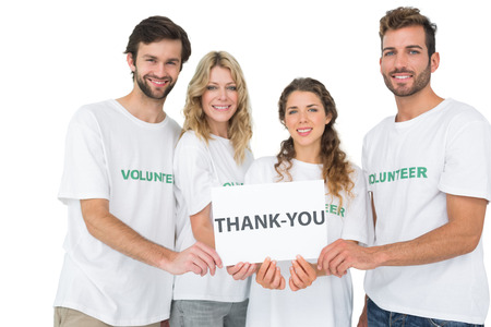Group portrait of happy volunteers holding 'thank you' board over white background photo