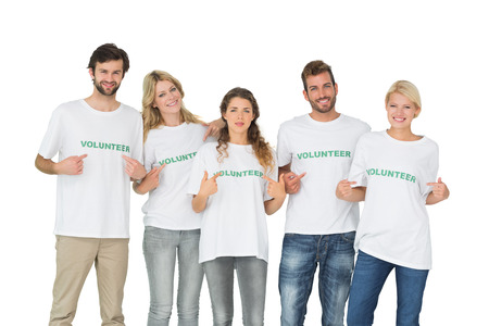 selfless: Group portrait of happy volunteers pointing to themselves over white background