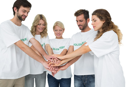 Group of young volunteers with hands together over white background photo