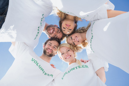 volunteerism: Low angle portrait of happy volunteers forming a huddle against blue sky Stock Photo
