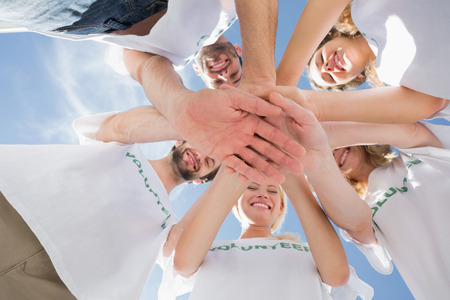volunteerism: Low angle view of happy volunteers with hands together against blue sky Stock Photo