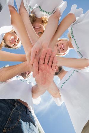 altruismo: �ngulo de visi�n baja de voluntarios felices con las manos juntas contra el cielo azul Foto de archivo