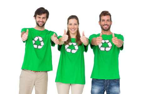 Portrait of young people in recycling symbol t-shirts gesturing thumbs up over white background