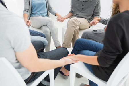 Group therapy in session sitting in a circle with therapist photo