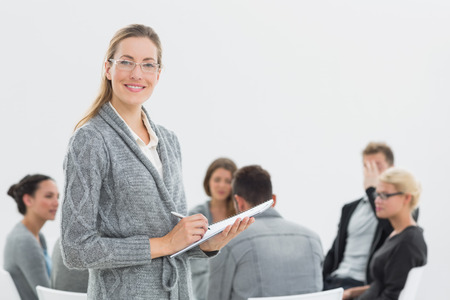female therapist: Portrait of a smiling female therapist with group therapy in session in background Stock Photo