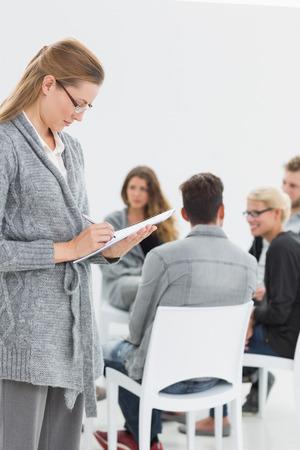 terapia de grupo: Escritura terapeuta de sexo femenino serio observa con la terapia de grupo en la sesi�n en el fondo Foto de archivo