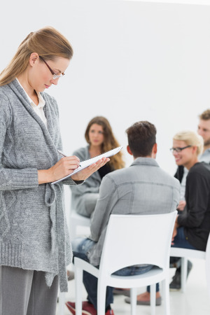 female therapist: Serious female therapist writing notes with group therapy in session in background Stock Photo