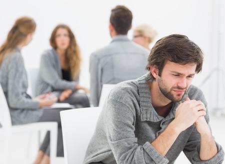terapia de grupo: La terapia de grupo en la sesi�n que se sienta en un c�rculo con el terapeuta mientras que el hombre en primer plano