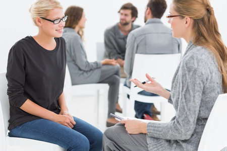 counseling session: Group therapy session in circle with therapist and client in foreground Stock Photo
