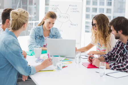 business casual: Young casual business people sitting around conference table in a bright office