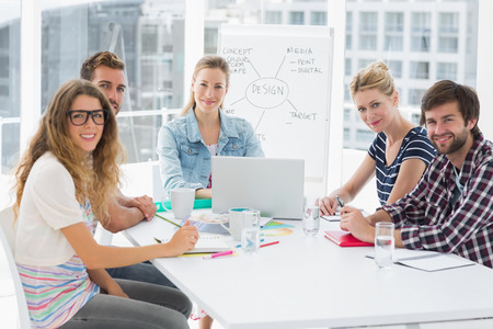 casual business: Young casual business people sitting around conference table in a bright office