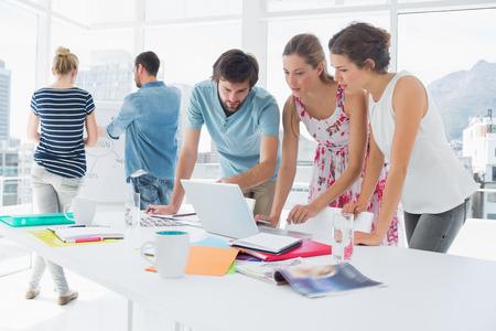 reunion de personas: Casual gente de negocios jovenes que usan la computadora port�til junto en una oficina brillante Foto de archivo