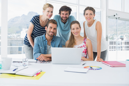 casual business: Young casual business people using laptop together in a bright office Stock Photo