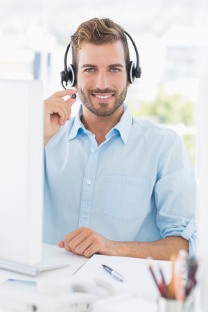 Portrait of a casual young man with headset using computer in a bright office photo