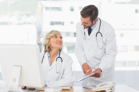 Two doctors using digital tablet by computer at medical office photo