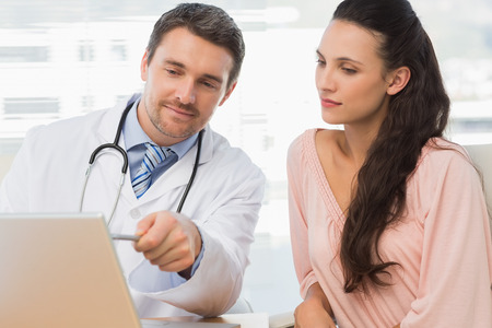 Male doctor showing something on laptop to patient in medical office photo