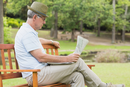 Side view of a relaxed senior man reading newspaper at the park photo