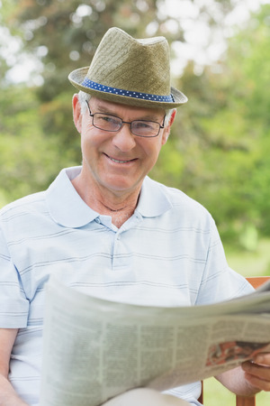 Smiling relaxed senior man reading newspaper at the park photo