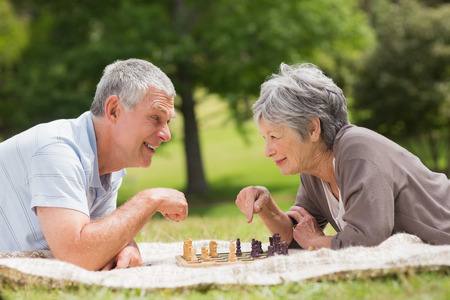 Side view of a happy senior couple playing chess at the park photo