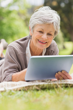 Smiling senior woman using digital tablet while lying at the park photo